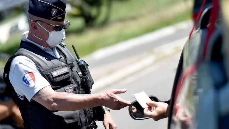 Un agent de police vérifie une attestation de déplacement et son justificatif, à Saint-Etienne (Loire), le 20 mai 2020. (R?MY PERRIN / MAXPPP)