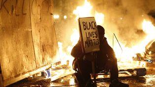 Un manifestant pendant les affrontements à Ferguson (Missouri, Etats-Unis), à la suite de l'acquittement du policier qui a abattu un jeune noir l'été dernier, le 25 novembre 2014. ( STEPHEN LAM / REUTERS)