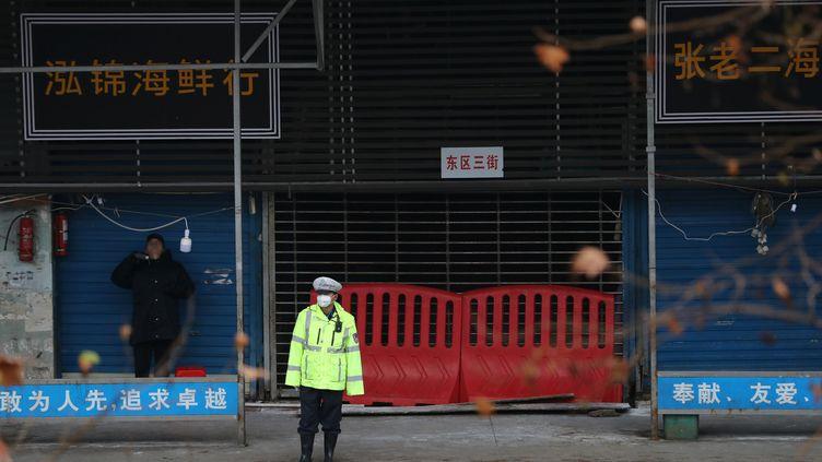 Un policier devant le marché aux poissons fermé de Wuhan (Chine), le 10 janvier 2020. (DARLEY SHEN / REUTERS)
