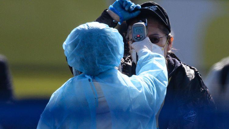 """Une personne mesure la température corporelle d'un passager débarquant du navire de croisière """"Diamond Princess"""", à Yokohama (Japon) le 21 février 2020. (PHILIP FONG / AFP)"""
