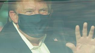 Donald Trumpsalue un groupe de supporters depuis une voiture, le 4 octobre 2020, devant l'hôpital Walter Reed, à Bethesda, dans le Maryland. (ALEX EDELMAN / AFP)