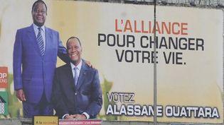 Affiche de campagne de l'alliance du RHDP photographiée le 21 novembre 2010 dans les rues d'Abidjan, la capitale ivoirienne. On y voit Henri Konan Bédié, le président du PDCI (debout) et Alassane Ouattara, l'actuel président ivoirien et leader du RDR. (SIA KAMBOU / AFP)