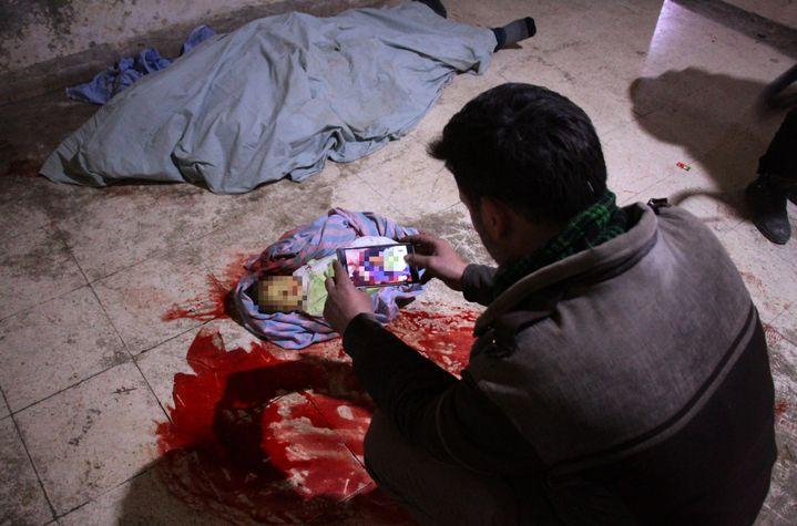 Un homme prend en photo le cadavre de son bébé, dans l'hôpital de Douma, dans l'enclave rebelle de la Ghouta orientale, près de Damas (Syrie), le 19 février 2018. (HAMZA AL-AJWEH / AFP)