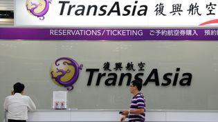 Des journalistes attendent devant le bureau de la compagnie TransAsia, à l'aéroport de Taiwan, mercredi 23 juillet 2014. (SAM YEH / AFP)