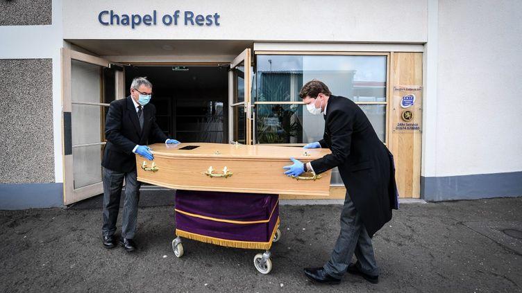 Des employés des pompes funèbres déplacent le cerceuil d'une femme morte du Covid-19 àFerryden, en Ecosse, le 4 mai 2020. (ANDY BUCHANAN / DIGITAL / AFP)