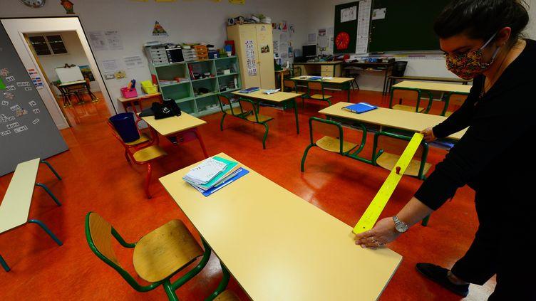 Une enseignante mesure la distance entre les tables à l'école élémentaire Jean-Jaurès de Cenon près de Bordeaux, le 11 mai 2020 (photo d'illustration) (MEHDI FEDOUACH / AFP)