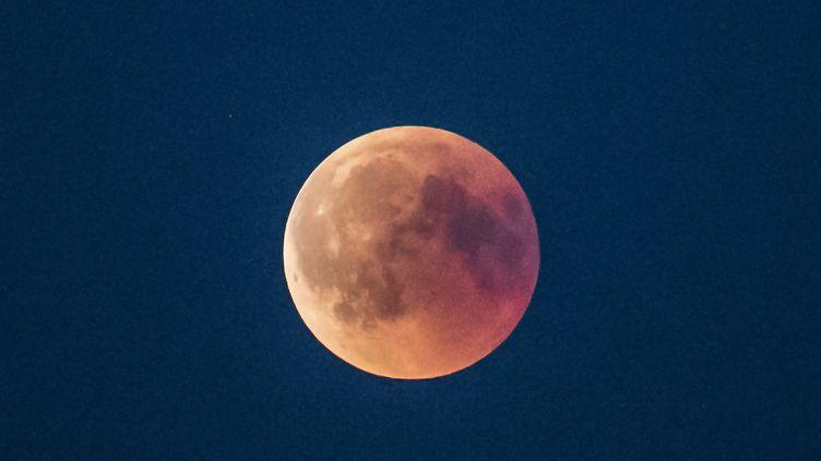 """A Roskilde (Danemark), l'éclipse n'a pas été masquée par les nuages, révélant une lune couleur """"brique"""". (MADS CLAUS RASMUSSEN / AFP)"""