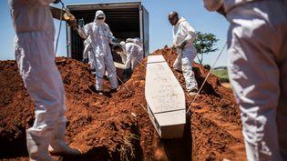 Des employés de la morgue de Johannesburg, en Afrique du Sud, enterrent un corps non-identifié au cimetière Olifantsvlei, le 27 février 2019. Les cadavres non réclamés reposent à la morgue durant un maximum de 30 jours, avant d'être inhumés. (GUILLEM SARTORIO / AFP)