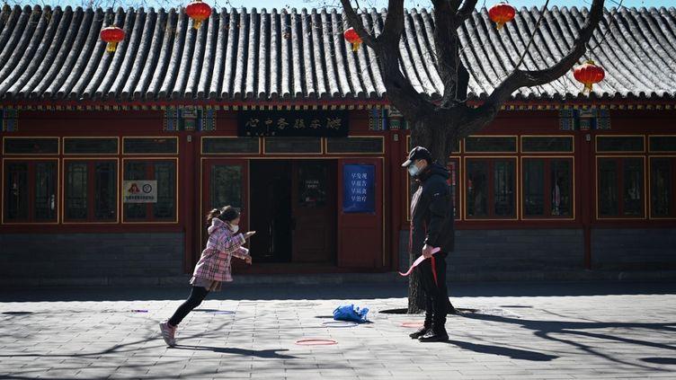 Une petite fille joue avec son père dans un parc de Pékin, le 14 mars 2020, en Chine. (WANG ZHAO / AFP)