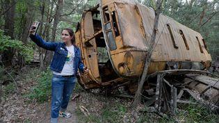 Une touriste se photographie devant un autobus abandonné, lors d'une visite à Tchernobyl (Ukraine), le 7 juin 2019. (MAXPPP)