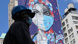 Un passant circule devant une fresque, le 7 mai 2020 à New York (Etats-Unis). (ANGELA WEISS / AFP)