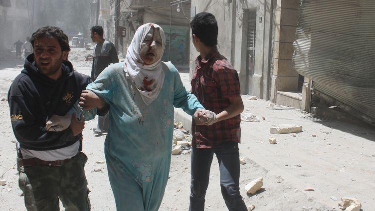 Des Syriens aident une femme blessée lors de combats à Alep, le 18 mai 2014. (TAMER AL-HALABI / ALEPPO MEDIA CENTRE / AFP)