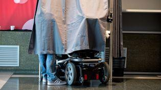 Une personne handicapée dans un bureau de vote à Evry (Essonne), le 6 décembre 2015. (NICOLAS MESSYASZ / SIPA)