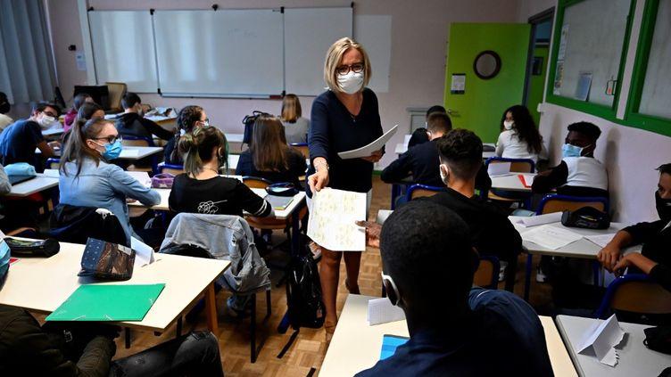 Un enseignante distribue des documents à ses élèves dans une classe du lycée de Brequigny à Rennes, le 1er septembre 2020 (illustration). (DAMIEN MEYER / AFP)