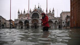 Une femme traverse la place Saint-Marc inondée, à Venise (Italie), le 13 novembre 2019. (MARCO BERTORELLO / AFP)