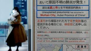 Une femme porte un masque de protection à l'aéroport de Haneda à Tokyo (Japon), le 20 janvier 2020. (KIM KYUNG HOON / REUTERS)