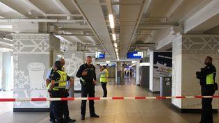 Des policiers installent un périmètre de sécurité après une attaque au couteau à la gare centrale d'Amsterdam (Pays-Bas), le 31 août 2018. (GERMAIN MOYON / AFP)