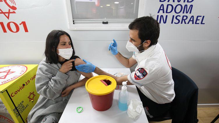 Une jeune israelienne reçoit une dose de vaccin contre le Covid-19 à Tel-Aviv, le 18 février 2021. (MOSTAFA ALKHAROUF / ANADOLU AGENCY)