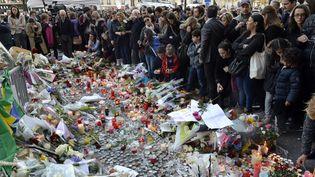 Des Parisiens rendent hommage aux victimes des attentats du 13 novembre, près du Bataclan, le 15 novembre 2015. (MIGUEL MEDINA / AFP)