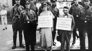 """JUSQU''AU DERNIER, LA DESTRUCTION DES JUIFS D''EUROPE'(ÉPISODE 2)Entre 1938 et 1945, à Hambourg, ces S.S. et S.A. entourent deux jeunes gens, l'un Juif, l'autre non-juive, qu'ils promènent à travers la ville afin de montrer aux foules """"l'exemple à ne pas suivre"""". La jeune fille allemande porte une pancarte qui proclame : """"Je suis une salope et je me permets de coucher avec des Juifs"""". Le jeune garçon juif à côté d'elle porte également une pancarte qui dit : """"En tant que Juif, je peux faire monter des jeunes filles allemandes dans ma chambre"""". Il s'agit de forcer l'opinion par la terreur de l'humiliation, à croire à l'impureté d'une union mixte (entre une Juif et un """"aryen""""). (KEYSTONE-FRANCE)"""