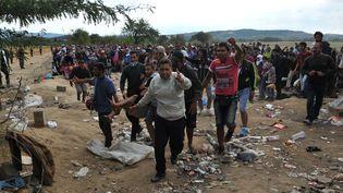 Des migrants tentent de passer la frontière entre la Grèce et la Macédoine, le 21 août 2015. (SAKIS MITROLIDIS / AFP)