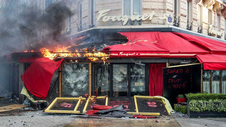 """Le store en flammes du Fouquet's le 16 mars 2019 sur les Champs-Elysées à Paris lors de la manifestation des """"gilets jaunes"""". (ZAKARIA ABDELKAFI / AFP)"""