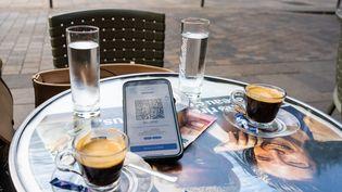 Un téléphone montrant un pass sanitaire, posé sur la table d'une terrasse, le 25 juillet 2021 à Toulouse (Haute-Garonne). (SANDRINE MARTY / HANS LUCAS / AFP)