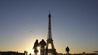 Des touristes près de la tour Eiffel, à Paris, le 14 janvier 2017. (LUDOVIC MARIN / AFP)