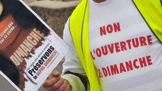 Un homme brandit une pancarte lors d'une manifestation contre le travail dominical, le 1er novembre 2009, devant un supermarché de Podensac (Gironde). (PIERRE ANDRIEU / AFP)