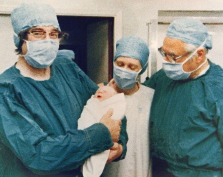 Louise Brown dans les bras du physiologue Robert Edwards (gauche) à côté du gynécologue Patrick Steptoe (droite), à l'hôpital d'Oldham le 25 juillet 1978. (KEYSTONE / GETTY IMAGES)