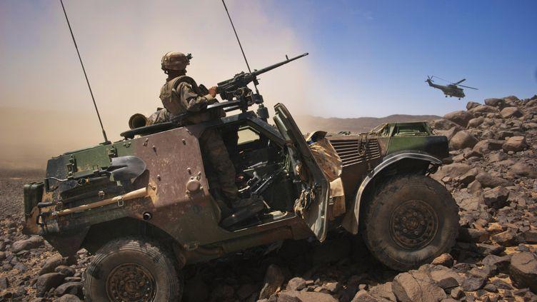 Un soldat français monte la garde à bord d'un véhicule blindé, alors qu'un hélicoptère décolle dans la vallée de Terz (nord du Mali), le 21 mars 2013. (FRANCOIS RIHOUAY / REUTERS)