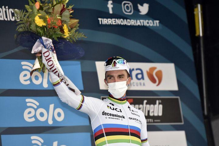 Sur le podium de la Flèche Wallone le 11 mars 2021, Julian Alaphilippe arbore - comme toujours -une casquette, mais celle-ci est aux couleurs de son maillot de champion du monde. (TOMMASO PELAGALLI / AFP)