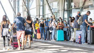 Des passagers font la queue devant l'aéroport Félix-Eboué, à Cayenne (Guyane), le 10 juillet 2020. (JODY AMIET / AFP)