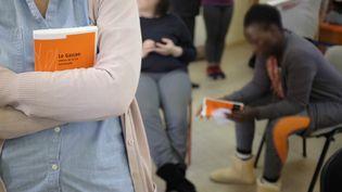 """Des femmes détenues de la maison d'arrêt de Versaillesen possession du livre d'Olivia Resenterra, """"Le garçon""""  (Natalie HANDEL / AFP)"""