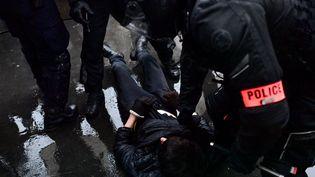 """Un manifestant est interpellé par des policiers lors de la manifestation contre la proposition de loi """"Sécurité globale"""", à Paris, le 12 décembre 2020. (MARTIN BUREAU / AFP)"""