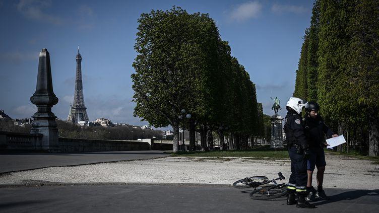 Un policier contrôle un homme à Paris, le 31 mars 2020 (illustration). (PHILIPPE LOPEZ / AFP)