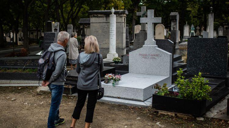 Des anonymes observent la tombe qui accueillera la dépouille de Jacques Chirac, vendredi 27 septembre 2019 au cimetière du Montparnasse, à Paris. (MARTIN BUREAU / AFP)