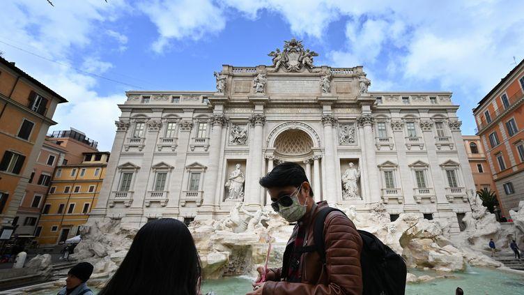 Des touristes portent des masques de protection devant la fontaine de Trevi, dans le centre de Rome, le 3 mars 2020. (ALBERTO PIZZOLI / AFP)