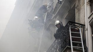 Un riverain est évacué par les pompiers après l'explosion d'une boulangerie au coin de la rue Sainte-Cécile et de la rue de Trévise, samedi 12 janvier, peu avant 9h du matin. (THOMAS SAMSON / AFP)