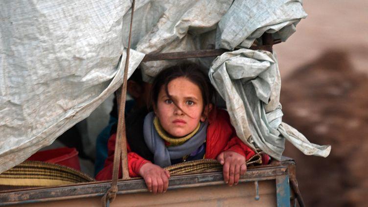 Une fillette syrienne déplacée sur le chemin du camp de Deir al-Ballut, le long de la frontière avec la Turquie, le 19 février 2020. (RAMI AL SAYED / AFP)