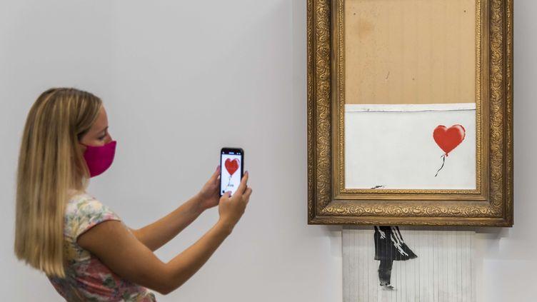 """La toile autodétruite de Banksy, auparavant """"La fille au ballon' et rebaptisée """"Love is in the Bin"""",exposée le 3 septembre 2021 dans la galerie de la maison d'enchères Sotheby's à Londres (G-B), qui le remet en vente le 14 octobre 2021. (GUY BELL / SHUTTERSTOCK / SIPA)"""