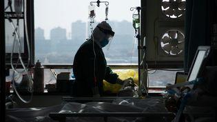 Un membre du personnel soignant d'un hôpital de Wuhan (Chine) s'occupe d'un malade à l'isolement en pleine épidémie de coronavirus, le 22 février 2020. (CHINA DAILY CDIC / REUTERS)