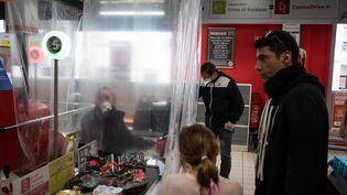 Les employés des commerces alimentaires sont sur le pont pendant la crise sanitaire. Cette salariée est protégée par un rideau en plastique à Nantes (Loire-Atlantique), le 20 mars 2020. (J?R?MIE LUSSEAU / HANS LUCAS / AFP)