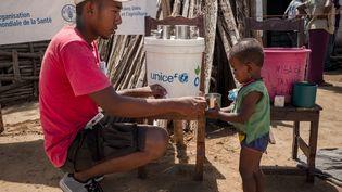 Un membre d'Action contre la Faim donne de l'eau à un enfant souffrant de malnutrition à Ifotaka (Madagascar), le 14 décembre 2018. (RIJASOLO / AFP)