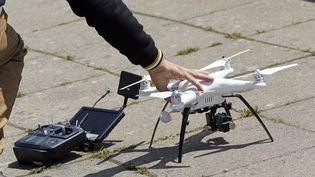 Un homme tient un drone, à Dijon (Côte-d'Or), le 6 août 2015. (CHRISTOPHE LEHENAFF / PHOTONONSTOP / AFP)