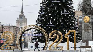 Un homme marche à côté d'une décoration de Noël dans le centre de Moscou (Russie), le 24 décembre 2020. (ALEXANDER NEMENOV / AFP)