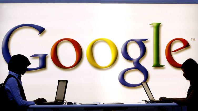 Deux internautes utilisent un ordinateur sur le stand Google à la foire du livre de Francfort, le 8 octobre 2006. (TORSTEN SILZ / DDP / AFP)