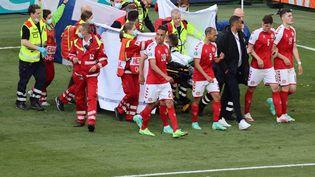 Les joueurs danois rassemblés autour de la civière qui évacue Christian Eriksen à Copenhague, le 12 juin 2021. (WOLFGANG RATTAY / AFP)