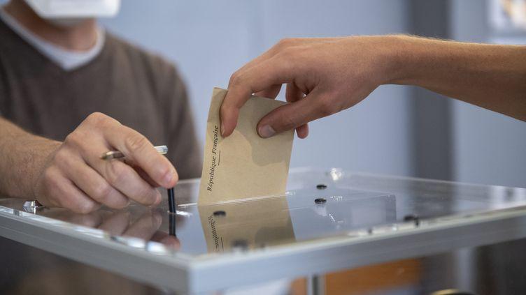 Une personne vote pour les élections régionales et départementales, le 27 juin 2021 à Dijon (Côte-d'Or). (EMMA BUONCRISTIANI / MAXPPP)