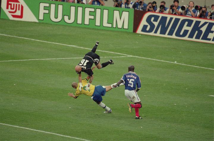 Fabien Barthez boxe un ballon au-dessus de l'attaquant brésilien Ronaldo, le 12 juillet 1998 en finale de la Coupe du monde, au Stade de France à Saint-Denis (Seine-Saint-Denis). (BOB MARTIN / SPORTS ILLUSTRATED / GETTY IMAGES)